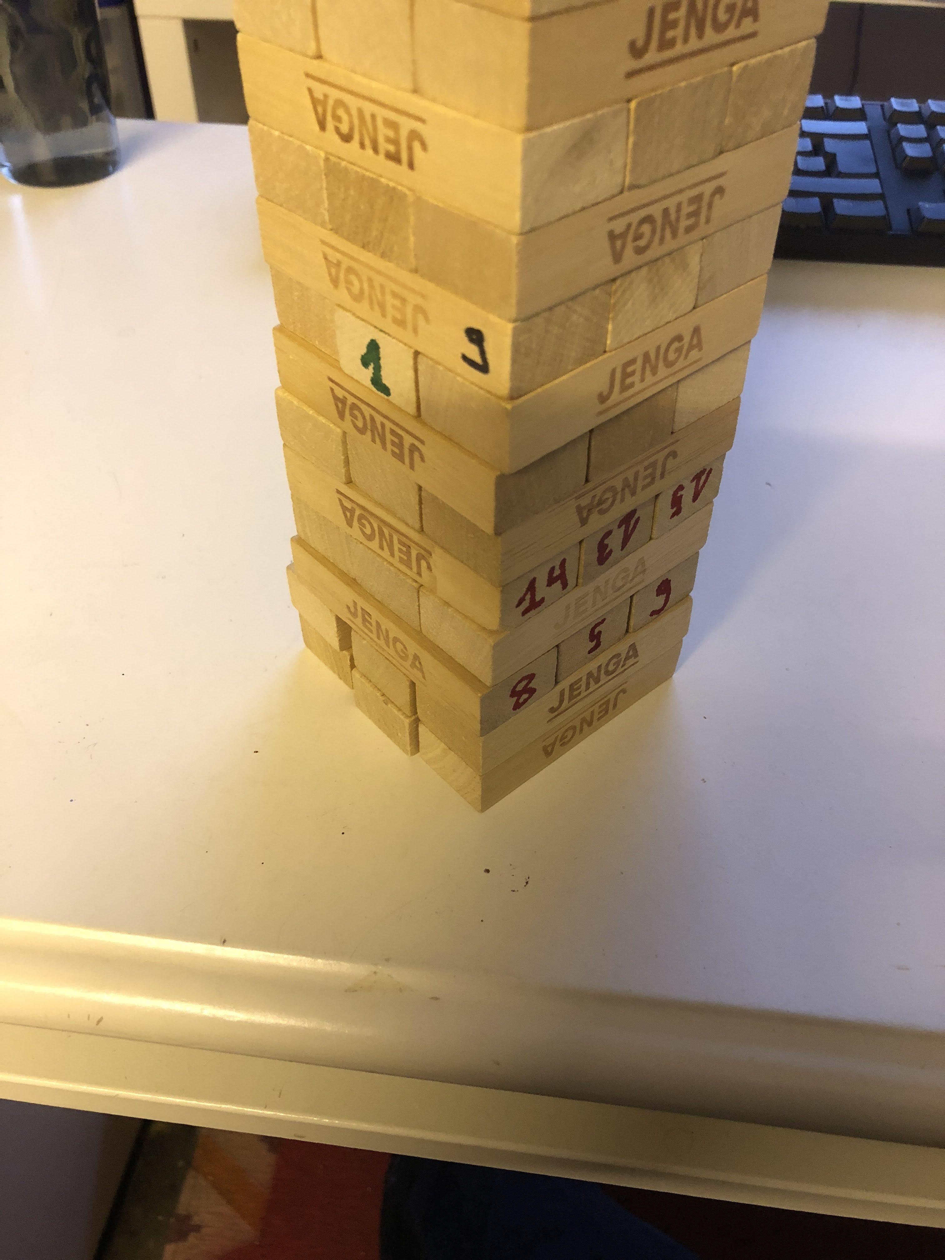 Agile Spiele: Agile Jenga. Ein Turm mit Bauklötzen mit Nummern in unterschiedlichen Farben.